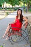 Beautiful fashionable girl sitting on park bench full body Royalty Free Stock Image