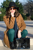 Beautiful fashionable girl sitting in park on sunny autumn day Royalty Free Stock Photography