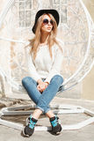 Beautiful fashionable girl sitting in a white suspended chair. Royalty Free Stock Images