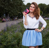 Beautiful fashionable Girl with vintage pink camera in the park in warm summer evening Stock Photos