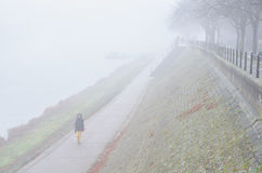 Beautiful fashionable girl walking beside river in misty autumn Stock Photo