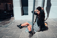 Beautiful fashionable lady sitting on old street Royalty Free Stock Photos