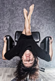 Beautiful fashionable lady wearing a gothic black dress with high collar, poses upside down on a leather armchair. On a grey background Royalty Free Stock Photo