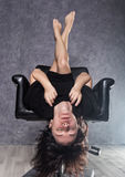 Beautiful fashionable lady wearing a gothic black dress with high collar, poses upside down on a leather armchair. On a grey background Stock Photo