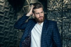 Beautiful fashionable man fixes his hair. dressed in suit royalty free stock images