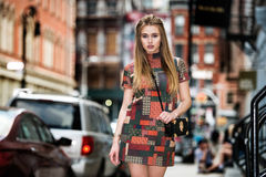 Beautiful fashionable model girl walking on New York City street wearing short elegant dress with a bag Royalty Free Stock Photos