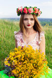 Beautiful fashionable pretty gorgeous girl in dress on the flowers field. Nice girl with wreath of flowers on her head and bouquet Stock Image