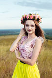 Beautiful fashionable pretty gorgeous girl in dress on the flowers field. Nice girl with wreath of flowers on her head and bouquet Stock Photo