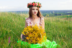 Beautiful fashionable pretty gorgeous girl in dress on the flowers field. Nice girl with wreath of flowers on her head and bouquet Stock Images