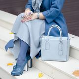 Beautiful fashionable shoes on women`s leg. Stylish  ladies accessories. blue shoes and bag, coat with dress or skirt. Royalty Free Stock Photos