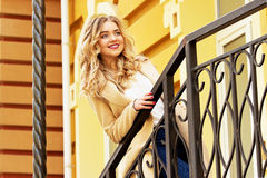 Beautiful and fashionable smiling blond hair girl walking the city. Womens fashion. Stock Photography