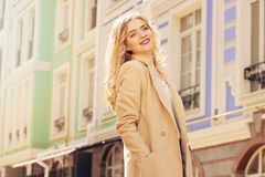 Beautiful and fashionable smiling blond hair girl walking the city. Womens fashion. Royalty Free Stock Images