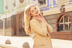Beautiful and fashionable smiling blond hair girl walking the city. Womens fashion. Royalty Free Stock Photography