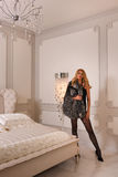 Beautiful fashionable woman in black provocative lingerie bodysuit and luxury fur coat posing in modern bedroom interior. Stock Photography