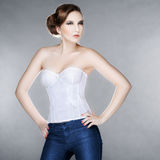 Beautiful fashionable woman in a corset. On a gray background Royalty Free Stock Photo