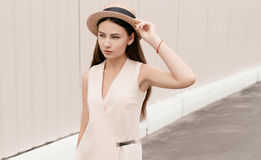 Beautiful fashionable woman in a hat walks through the city. Business woman in a hat Royalty Free Stock Photography