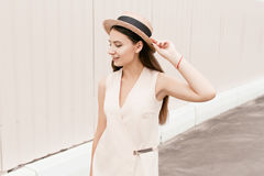 Beautiful fashionable woman in a hat walks through the city. Business woman in a hat Stock Photography