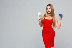 Beautiful fashionable woman holds the money and credit card. Stylish slender woman in a red dress with red lips. Beautiful hair, necklace Royalty Free Stock Image