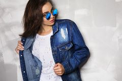 Wwoman in round sunglasses posing near a gray wall at studio. Beautiful fashionable woman with long hair in round sunglasses posing near a gray wall at studio royalty free stock images