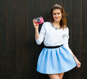 Beautiful fashionable woman with pink vintage camera, a blue short skirt posing near the wooden wall of a warm summer evening Royalty Free Stock Image
