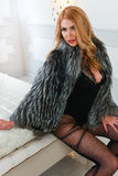 Beautiful fashionable woman posing sexy in black lingerie bodysuit and luxury fur coat at modern bedroom. Stock Photos