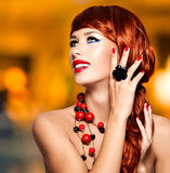 Beautiful fashionable woman with red nails and red hairs stock photography