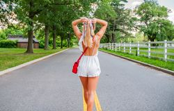 Beautiful fashionable woman walking on the road in summer stock photography
