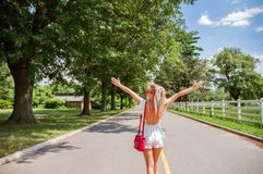 Beautiful fashionable woman walking on the road in summer stock photo