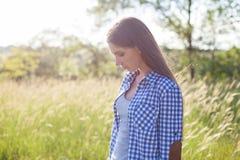 Beautiful fashionable woman walks across the field royalty free stock image
