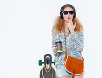 Beautiful fashionable young blond woman with a longboard, cup of coffee and cool headphones in surprise covers her mouth with her Stock Photography