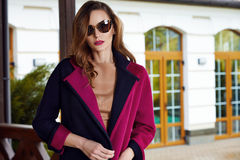 Beautiful fashionable young business woman wearing in ?rimson autumn coat and sunglasses with hairdo and makeup walking on a stree Royalty Free Stock Photo