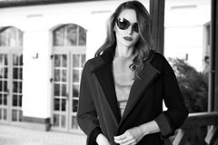 Beautiful fashionable young business woman wearing in ?rimson autumn coat and sunglasses with hairdo and makeup walking on a stree Stock Photos