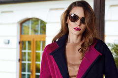 Beautiful fashionable young business woman wearing in ?rimson autumn coat and sunglasses with hairdo and makeup walking on a stree Stock Photography
