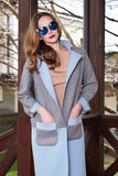 Beautiful fashionable young business woman wearing in ?rimson autumn coat and sunglasses with hairdo and makeup walking on a stree Stock Images