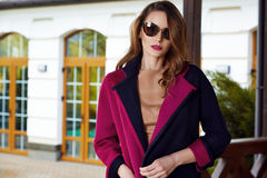 Beautiful fashionable young business woman wearing in ?rimson autumn coat and sunglasses with hairdo and makeup walking on a stree Stock Image