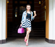 Beautiful fashionable young girl posing in a summer dress and denim jacket with a pink bag and multi-colored ice cream. Outdoor stock photography