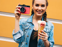 Beautiful fashionable young girl posing in a summer dress and denim jacket with pink vintage camera and multi-colored ice cream. O. Super Beautiful fashionable Royalty Free Stock Images