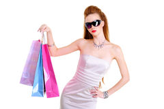 Beautiful fashionable young girl with purchases. The beautiful fashionable young girl with purchases in hands - isolated on white Stock Photography