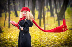 Beautiful fashionable young girl with red umbrella , red cap and red scarf in the park Royalty Free Stock Photos