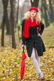 Beautiful fashionable young girl with red umbrella , red cap and red scarf in the park Stock Photos