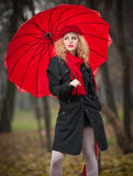 Beautiful fashionable young girl with red umbrella , red cap and red scarf in the park Royalty Free Stock Image