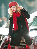 Beautiful fashionable young girl with red umbrella in the street Stock Images