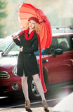 Beautiful fashionable young girl with red umbrella in the street Stock Image