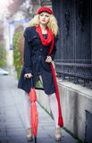 Beautiful fashionable young girl with red umbrella in the street Stock Photography
