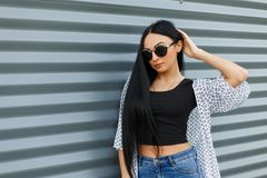 Beautiful fashionable young hipster woman in sunglasses with long black hair in a stylish white summer jacket in a black t-shirt stock images