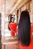 Beautiful fashionable young woman in beauty salon looking in mirror after makeup and hair care royalty free stock photos