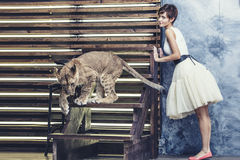 Beautiful fashionable young woman with a little alive lion cub. Beautiful fashionable young woman with a cute little alive lion cub Stock Photo
