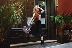 Beautiful fashionable young woman running with bag. City lifestyle. Female fashion. Full body portrait.  Royalty Free Stock Images