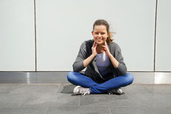 Beautiful fashionable young woman sit on street by the wall with Royalty Free Stock Image