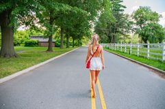 Beautiful fashionable woman walking on the road in summer stock images